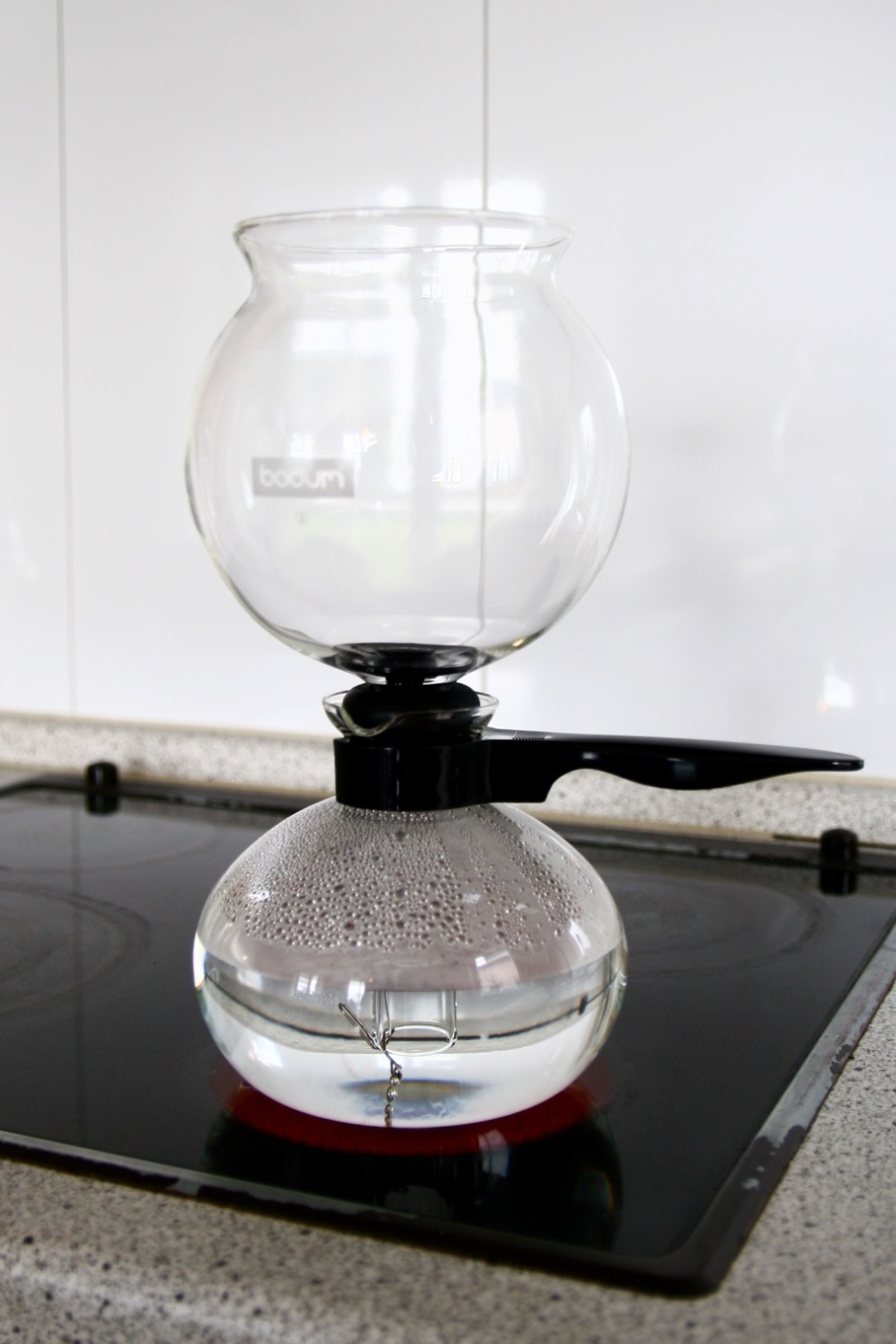 Position the Vacuum Coffee Maker over a heatsource and set it to a medium setting