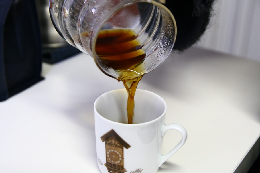 Serve the coffee into a pre-heated cup